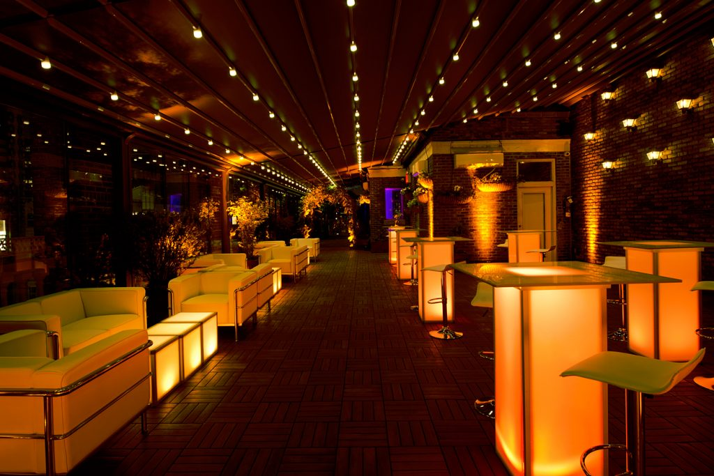terrace with orange illuminated furniture - Midtown Productions