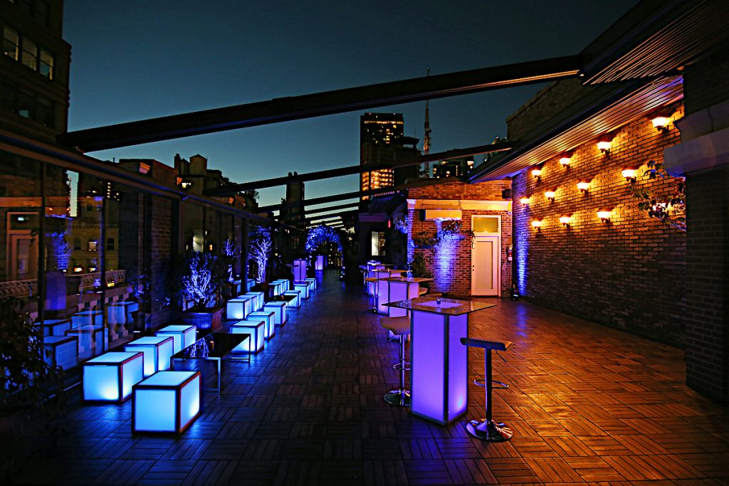furniture on terrace at night with view and open awning - NYC corporate event space